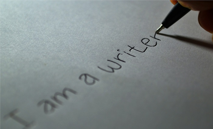 "A person writing, ""I am a writer"" on a piece of paper."
